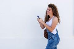 Sonrisa adolescente con caminar del teléfono móvil y de los auriculares Foto de archivo libre de regalías