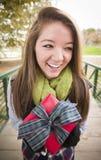 Sonrisa adolescente con el regalo envuelto con el arco afuera Imagenes de archivo