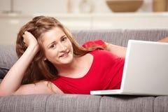 Sonrisa adolescente con la computadora portátil en el sofá en el país Fotografía de archivo libre de regalías
