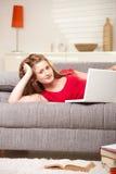 Sonrisa adolescente con la computadora portátil en el sofá en el país Imagenes de archivo
