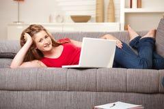 Sonrisa adolescente con la computadora portátil en el sofá en el país Foto de archivo