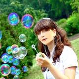 Sonrisa adolescente con las burbujas de jabón Fotos de archivo