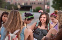 Sonrisa adolescente con los amigos en campus Imágenes de archivo libres de regalías