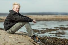 Sonrisa adolescente con los brazos alrededor de rodillas afuera Fotografía de archivo libre de regalías