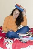 Sonrisa adolescente de la muchacha que se sienta con los libros en cama Imagenes de archivo