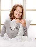 Sonrisa adolescente en cama Imagen de archivo