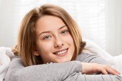 Sonrisa adolescente en cama Imágenes de archivo libres de regalías