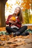 Sonrisa adolescente en la tela escocesa que sostiene una calabaza Imagen de archivo libre de regalías