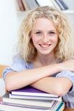 Sonrisa adolescente estudiando muchos libros Fotografía de archivo libre de regalías