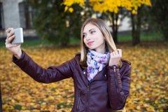 Sonrisa adolescente feliz de la muchacha durante caminar en parque del otoño Imagenes de archivo