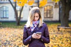 Sonrisa adolescente feliz de la muchacha durante caminar en parque del otoño Foto de archivo libre de regalías