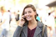 Sonrisa adolescente mirándole en el teléfono Foto de archivo libre de regalías