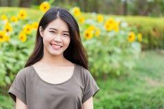 Sonrisa adolescente tailandesa asiática del retrato lindo con el girasol Fotos de archivo
