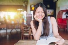 Sonrisa adolescente tailandesa de las mujeres asiáticas con el libro en café Fotografía de archivo