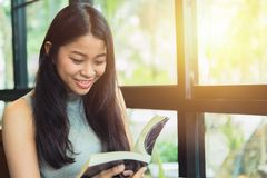 Sonrisa adolescente tailandesa de las mujeres asiáticas con el libro en café Imagenes de archivo