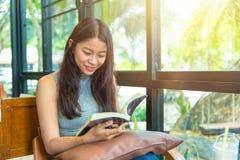 Sonrisa adolescente tailandesa de las mujeres asiáticas con el libro en cafetería Foto de archivo