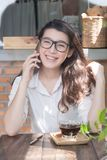 Sonrisa alegre joven de la mujer de negocios que se sienta en el café de la terraza, disfrutando de la comunicación en línea usan fotos de archivo