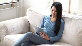 Sonrisa asiática de la mujer del retrato hermoso y feliz jovenes usando la tableta digital que se sienta en el sofá en la sala de metrajes