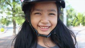Sonrisa asiática de la niña con el casco de seguridad del deporte de la felicidad que lleva almacen de video