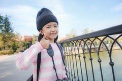 Sonrisa asiática de la niña y el mostrar pulgares para arriba con la felicidad para Fotos de archivo