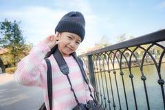 Sonrisa asiática de la niña y mostrar la muestra de la victoria con felicidad Imagen de archivo libre de regalías