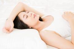 Sonrisa asiática hermosa del sueño de la mujer en cama comfortablemente foto de archivo libre de regalías