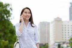 Sonrisa asiática de la llamada del teléfono celular de la mujer que mira el lado Fotos de archivo libres de regalías