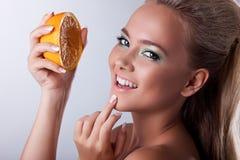 Sonrisa atractiva de la muchacha con la naranja del apretón fotos de archivo