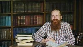 Sonrisa barbuda joven del hombre del retrato feliz en biblioteca y mirada en cámara foto de archivo