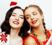 Sonrisa bastante feliz de los jóvenes novias rubias y morenas de la mujer el la Navidad en el sombrero rojo de santas y el día de Imagen de archivo libre de regalías