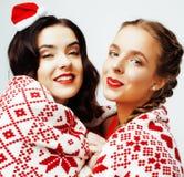 Sonrisa bastante feliz de los jóvenes novias rubias y morenas de la mujer el la Navidad en el sombrero rojo de santas y el día de Foto de archivo libre de regalías