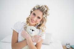 Sonrisa bigudíes de pelo que llevan bastante rubios que sostienen el oso de peluche Fotografía de archivo