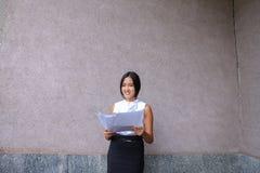 Sonrisa bonita de la muchacha, presentación, papel de los controles en manos y mirada del aw Foto de archivo libre de regalías