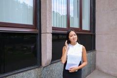 Sonrisa bonita de la muchacha, presentación, papel de los controles en manos y mirada del aw Foto de archivo