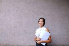 Sonrisa bonita de la muchacha, presentación, papel de los controles en manos y mirada del aw Fotografía de archivo