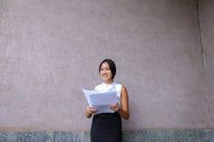 Sonrisa bonita de la muchacha, presentación, papel de los controles en manos y mirada del aw Imagen de archivo libre de regalías