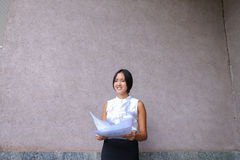 Sonrisa bonita de la muchacha, presentación, papel de los controles en manos y mirada del aw Imagen de archivo