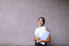 Sonrisa bonita de la muchacha, presentación, papel de los controles en manos y mirada del aw Imágenes de archivo libres de regalías