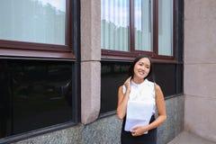 Sonrisa bonita de la muchacha, presentación, papel de los controles en manos y mirada del aw Fotos de archivo libres de regalías