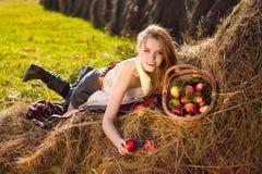 Sonrisa bonita joven de la mujer en la granja con muchos manzana foto de archivo