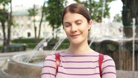 Sonrisa cerca encima del retrato de la mujer joven morena hermosa que sonríe en la ciudad Día de verano afuera almacen de video