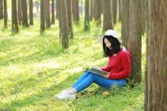 Sonrisa china asiática feliz de la muchacha de la belleza de la mujer y leído un libro en magro del parque de la primavera del bo Fotografía de archivo