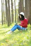 Sonrisa china asiática feliz de la muchacha de la belleza de la mujer y leído un libro en magro del parque de la primavera del bo Foto de archivo