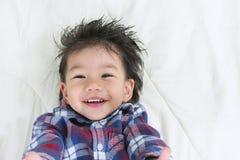 Sonrisa de Asia del bebé del retrato en cama con el espacio para el texto imágenes de archivo libres de regalías