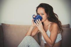 Sonrisa de consumición en la mujer adolescente del sofá con la taza Fotografía de archivo libre de regalías