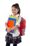 Sonrisa de la mochila y de los libros de la cartera de la pequeña colegiala que lleva hispánica linda Fotos de archivo