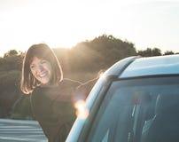 Sonrisa de la muchacha, aferrándose a una puerta de coche Concepto de viaje y de libertad Imagen de archivo