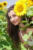 Sonrisa de la muchacha de Beautifull un campo del girasol Foto de archivo libre de regalías