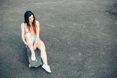Sonrisa de la muchacha del skater Muchacha del inconformista que se sienta en el monopatín Foto de archivo libre de regalías