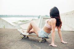 Sonrisa de la muchacha del skater Muchacha del inconformista que se sienta en el monopatín Fotografía de archivo